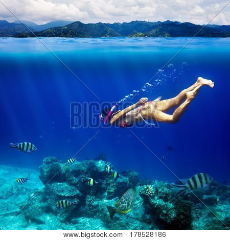 Underwater shoot of a young woman snorkeling in a tropical sea and coast mountain splitted by waterline. Design template