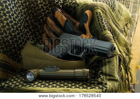 Composition of gun angle-head flashlight tactical gloves and strap belt lying on shemagh