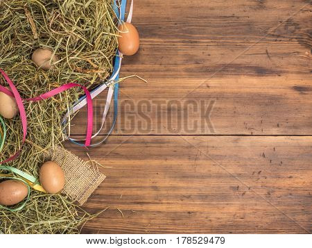Rural eco background with brown chicken eggs, colored ribbons and straw on the background of old wooden planks The view from the top. Creative background for Easter cards, menu or advertising