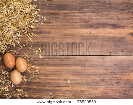 Rural eco background with brown chicken eggs and straw on the background of old wooden planks. The view from the top. Creative background for Easter cards, menu or advertising