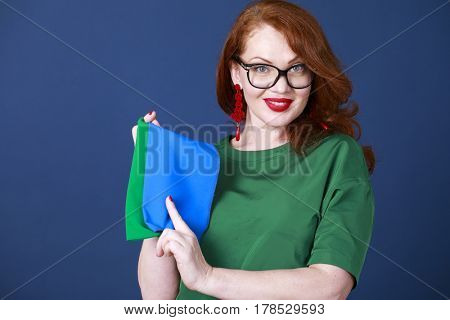 The stylist shows shawls of color-typing. Portrait of an adult woman on a blue background