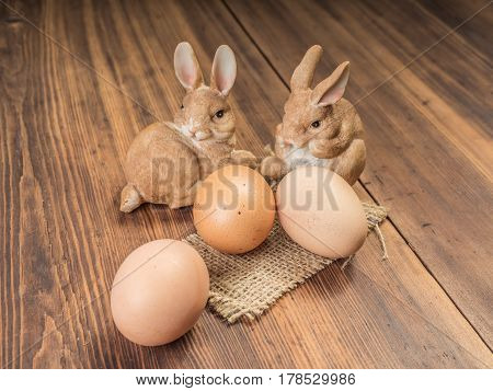 Easter bunnies on the background of wooden table from the old boards with burlap and brown chicken eggs. Background in rustic style for advertising or Easter greetings