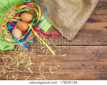 Rural eco background with brown chicken eggs, a piece of burlap, colored ribbons and straw on the background of old wooden planks. The view from the top. Creative background for Easter cards or menu