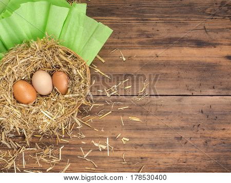 Brown eggs in hay nest. Rural eco background with brown chicken eggs and straw on the background of old wooden planks. Top view. Creative background for Easter cards, restaurant menu or design