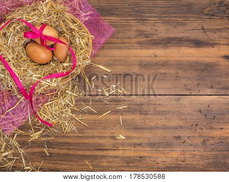 Brown eggs in hay nest. Rural eco background with brown chicken eggs, red ribbon and straw on the background of old wooden planks. Top view. Creative background for Easter cards or restaurant menu