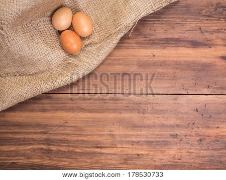 Chicken eggs on old rural wooden table boards and burlap vintage background, photo top view. Hessian, sacking texture with eggs on wooden background for design, Easter greetings card or advertisement