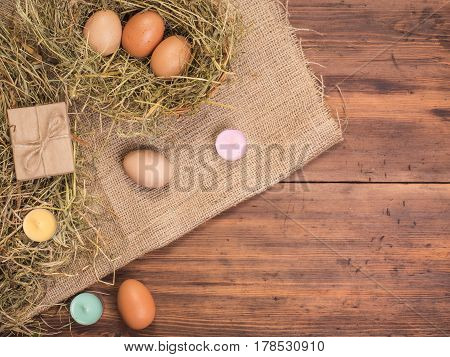 Rural eco background with brown chicken eggs, colored candles, gift box and straw on the background of old wooden planks. The view from the top. Creative background for Easter cards, menu, advertising