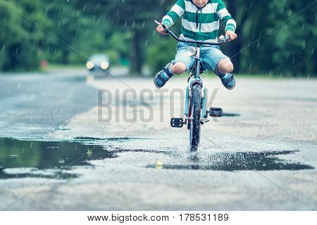child on a bicycle at asphalt road in summer. Bike in the park moving through puddle on rainy day