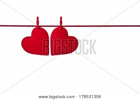 Two red felt hearts hanging on the rope fixed by clothespins isolated on white background