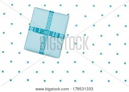 Blue gift box with bow on the polka dot background