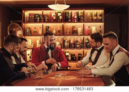 Group of upper class men playing poker in gentlemen's club