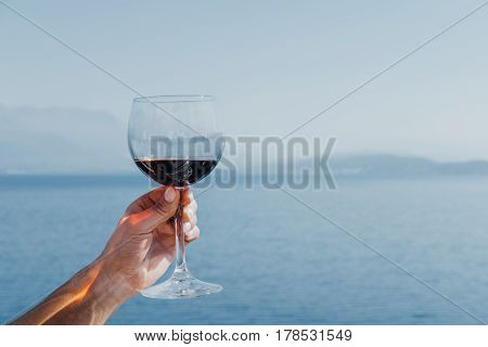 Glass with red wine in woman's hand on blue sea background.