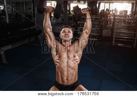 Athlete Muscular Bodybuilder Man Doing Exercises With Dumbbells In Gym