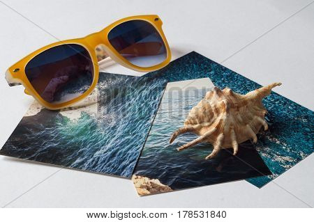 Yellow sunglasses shell and pictures with the image of the sea on white surface