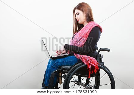 Young girl on wheelchair surfing web. Disabled woman with laptop. Health disability internet technology education concept.