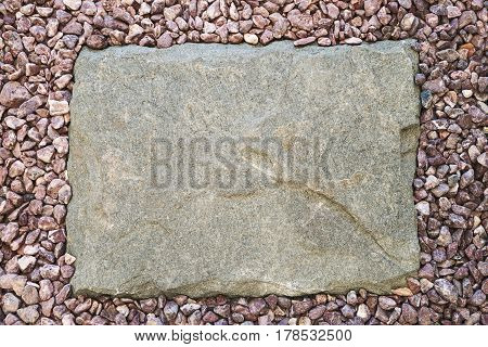 Stone slab around a pebble frame, top view with copy space.