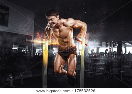 Muscular Bodybuilder Working Out In Gym Doing Exercises On Burning Fire Parallel Bars. Concept Sport