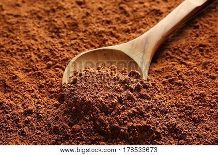Wooden spoon on cocoa powder background