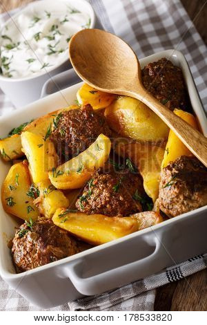 Meat Balls With Potatoes In A Baking Dish And Sour Cream Close-up On A Table. Vertical