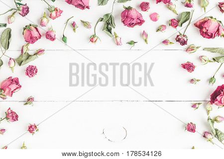 Flowers composition. Frame made of dried rose flowers on white wooden background. Flat lay top view