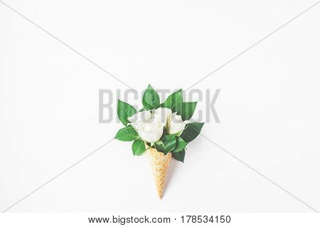 Flowers composition. Waffle cone with rose flowers. Flat lay top view