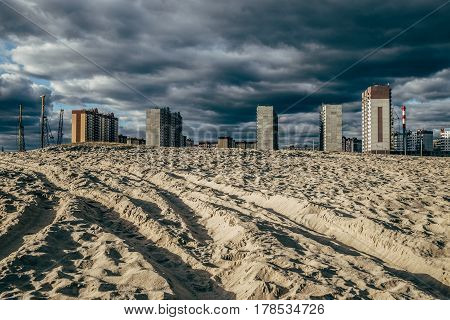 High-rise unfinished houses in the background of the desert sand. City and desert concept