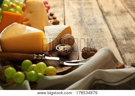 Delicious cheese, grape and nuts on wooden board