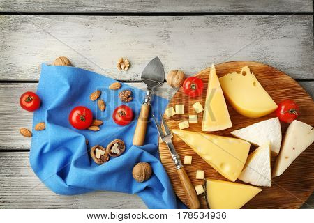 Wooden board with cheese, tomatoes and nuts on blue napkin