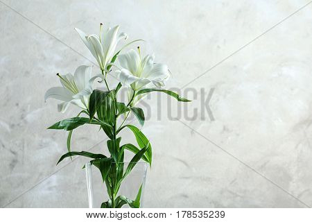 Beautiful white lilies in vase on light background