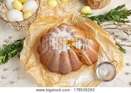 Delicious sliced Easter cake with food paper on fabric background