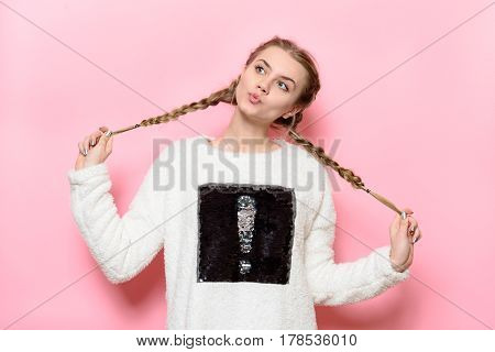 Beautiful cute girl having fun and holding pigtails posing near pink wall