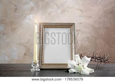 Photo frame, lily, crown of thorns and candle on beige background