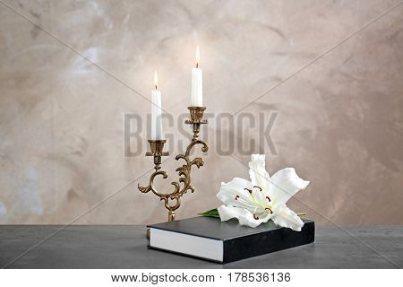 Lily, candles and Holy Bible on beige background