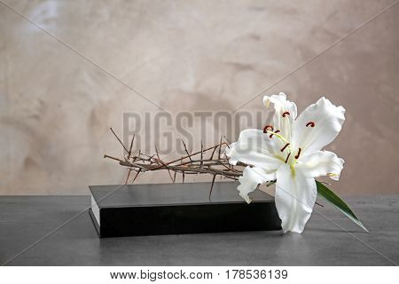 Crown of thorns, white lily and Holy Bible on beige background