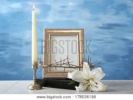 Photo frame, crown of thorns, lily, Holy Bible and candle on light background