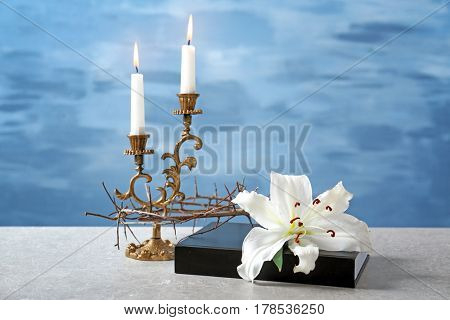 Holy Bible, lily, crown of thorns and candles on light background