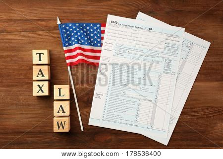 Wooden cubes with space for text and income tax form with American flag on table. Tax law concept