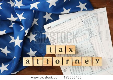 Wooden cubes with space for text and income tax form with American flag on table. Tax attorney concept