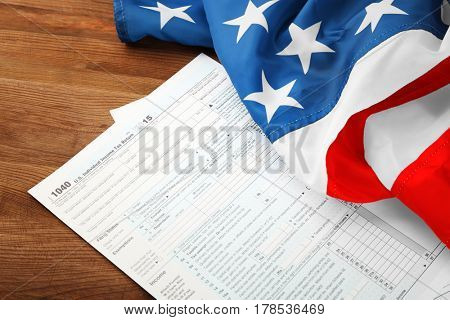 Individual tax return form and American flag on wooden table