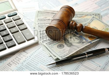 Judge's gavel and dollar banknotes on income tax form background