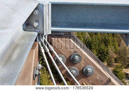 Wooden beams with screws in the structure. Assembling and connecting wooden beams. Detail of building connections. The construction of the observation tower