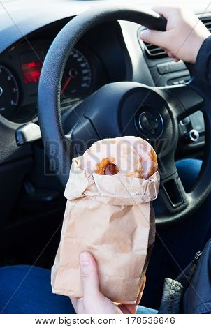 Man holding donuts craft bag sitting car