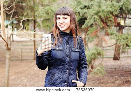 Beautiful girl making herself selfie mobile phone in a city park.
