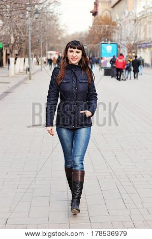 A young beautiful girl makes a leisurely walk along the central city street.