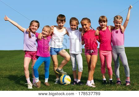 Portrait of seven little children with balls looking at camera and smiling