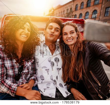 Cheerful teenagers taking self portrait on tricycle. Young man and women riding on tricycle bike and taking selfie.
