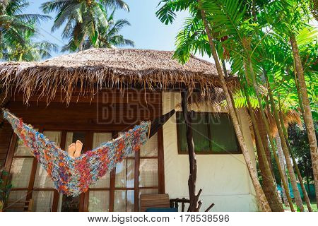 Legs sway in the hammock. Rest in a house on the beach. Tropical leisure. Feet in the sand after walking on the beach. Summer time.