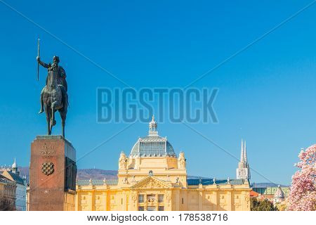 Panoramic view on King Tomislav statue, art pavilion and cathedral in Zagreb, Croatia, in spring. Croatian text on monument means