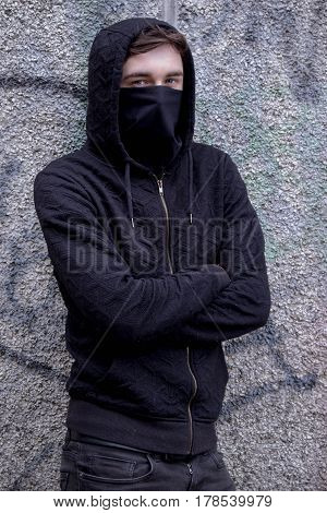 Teenage boy with his face hidden by a mask