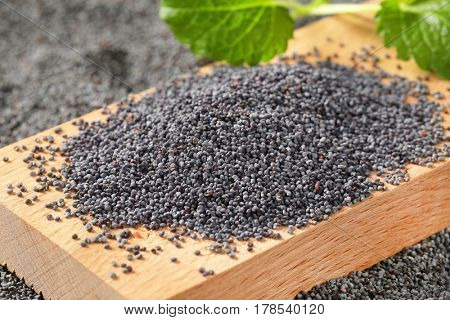 Whole black poppy seeds on cutting board and around it